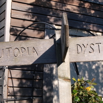 Sign pointing to utopia and dystopia