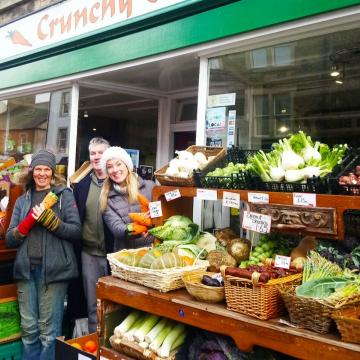 Group of people stood outside a greengrocers