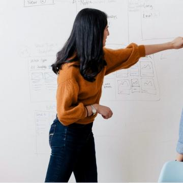 Two woman working at a whiteboard
