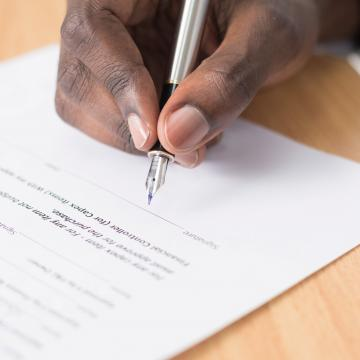 Male hand signing a contract